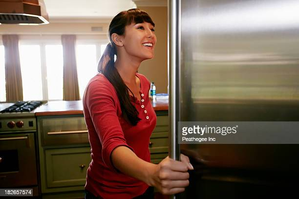 Mixed race woman looking through fridge