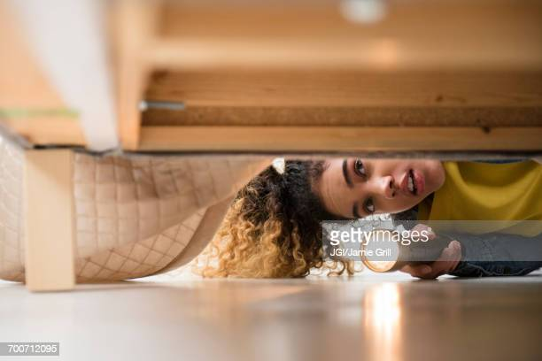 mixed race woman looking under bed with flashlight - ricerca foto e immagini stock