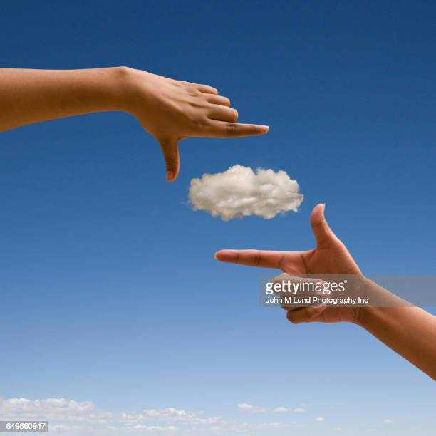 Mixed race woman making finger frame around cloud