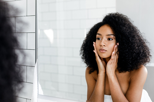 Mixed race woman massaging her face and looking at a mirror 875307848