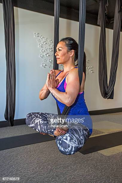 Mixed Race woman meditating hanging from silks