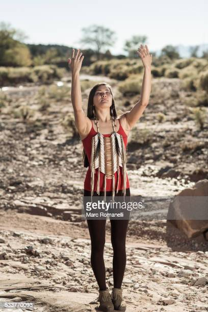 Mixed race woman meditating in remote desert landscape