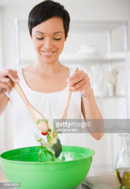 Mixed race woman mixing salad in kitchen
