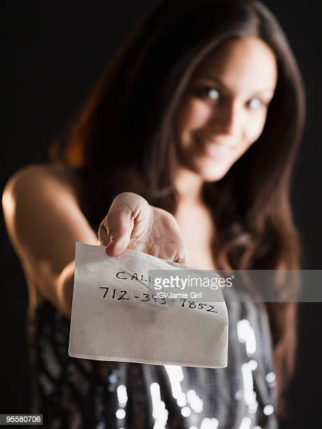Mixed race woman offering phone number on napkin