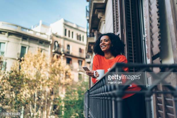 mixed race woman on christmas holiday in barcelona texting at the terrace - balcony stock pictures, royalty-free photos & images