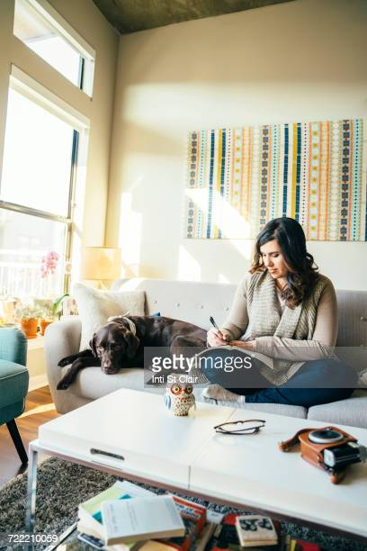 mixed race woman on sofa with dog writing in journal - dog pad foto e immagini stock