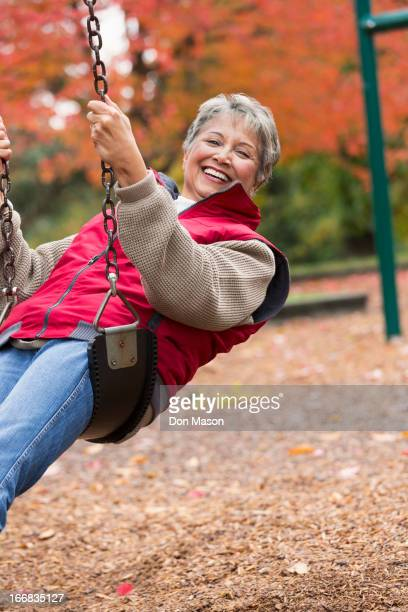 Mixed race woman on swing in park