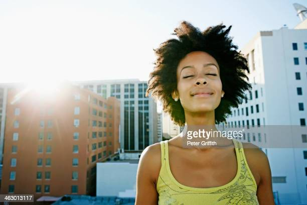 mixed race woman on urban rooftop - zen like stock pictures, royalty-free photos & images