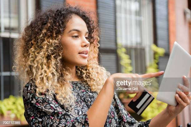 Mixed Race woman online shopping with digital tablet in city