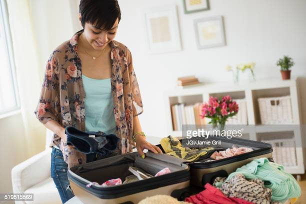 mixed race woman packing suitcase for vacation - packing stock pictures, royalty-free photos & images