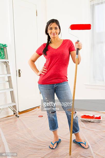 Mixed race woman painting room