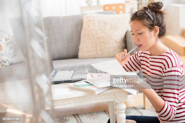 mixed race woman paying bills on laptop - financial bill stock pictures, royalty-free photos & images