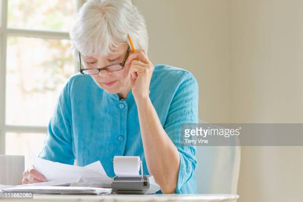 mixed race woman paying monthly bills - monthly event stock pictures, royalty-free photos & images
