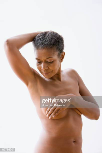 Mixed race woman performing breast exam on self