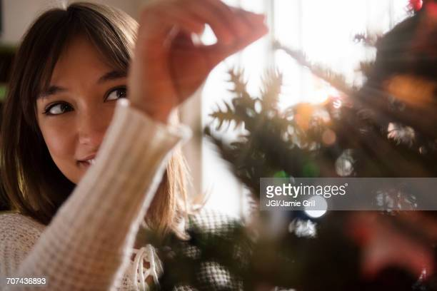 Mixed Race woman placing tinsel on Christmas tree