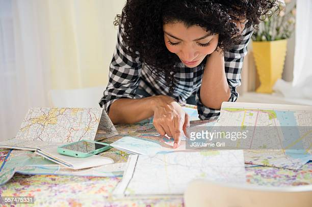 Mixed race woman planning road trip with maps