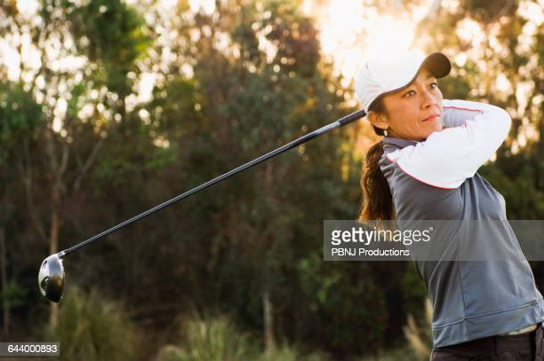 Mixed race woman playing golf on golf course