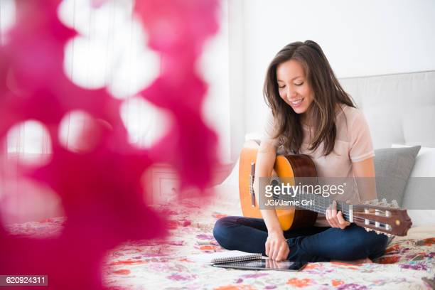 Mixed race woman playing guitar on bed