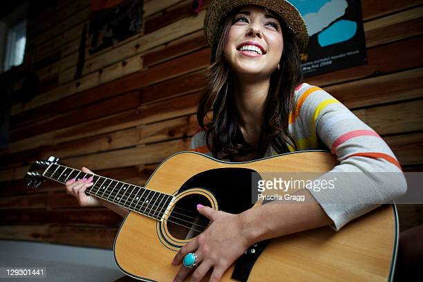 mixed race woman playing guitar - acoustic guitar stock pictures, royalty-free photos & images