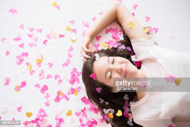Mixed race woman playing in confetti