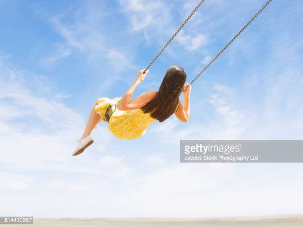 mixed race woman playing on swing against blue sky - columpiarse fotografías e imágenes de stock
