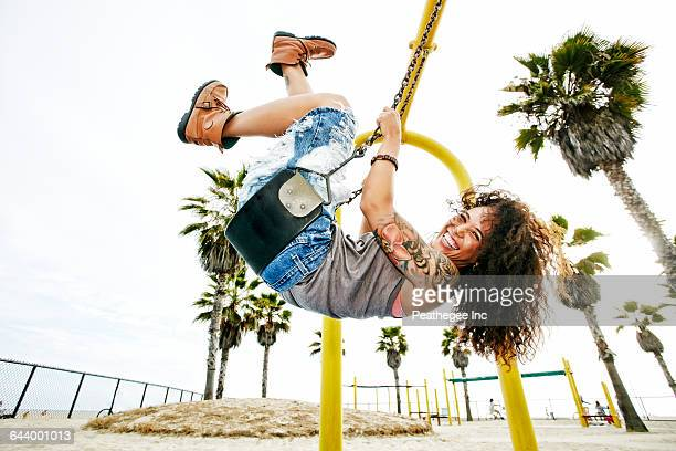 Mixed race woman playing on swing at beach