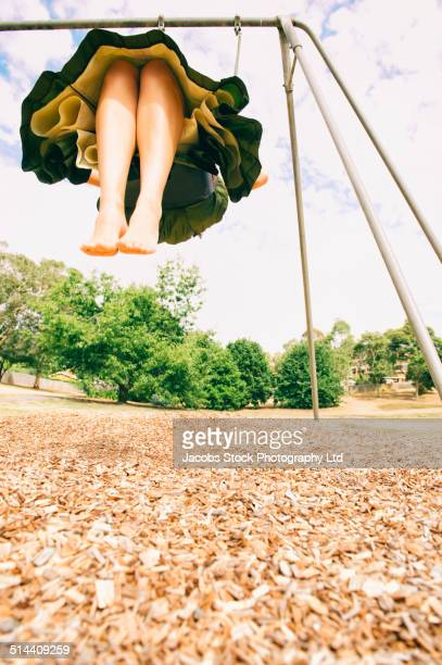 Mixed race woman playing on swing outdoors