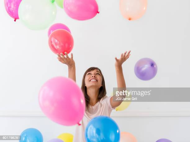 mixed race woman playing with balloons - 投げる ストックフォトと画像