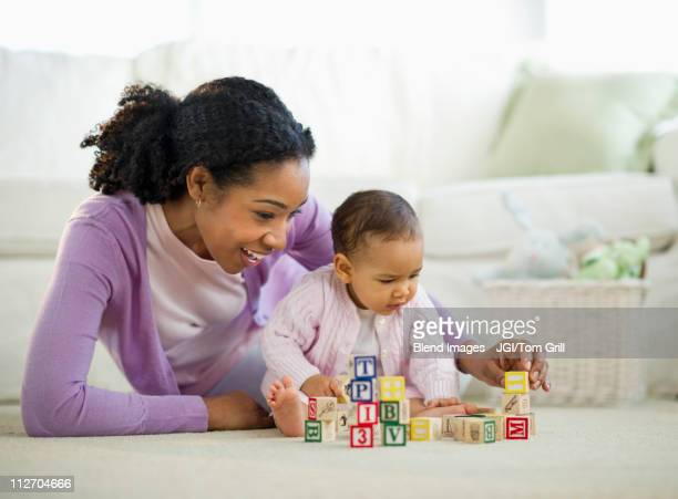 Mixed race woman playing with blocks with baby