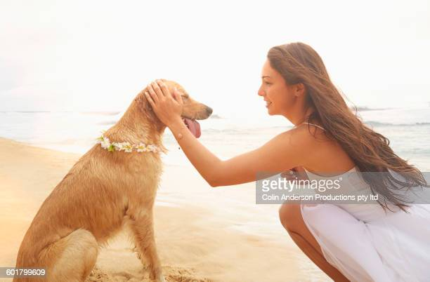 Mixed race woman playing with dog on beach