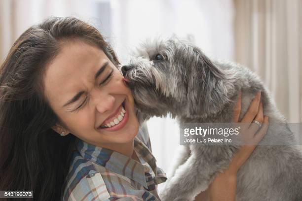 Mixed race woman playing with dog