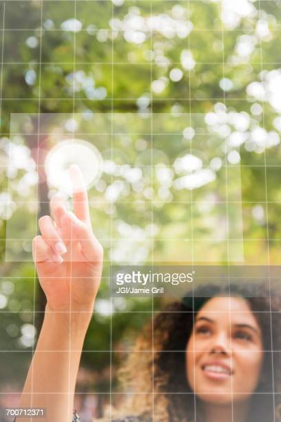 Mixed Race woman pointing to virtual screen outdoors