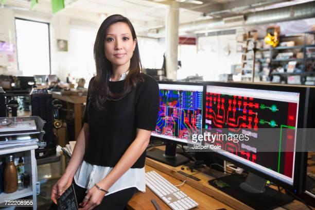 Mixed Race woman posing near circuits on computer monitors
