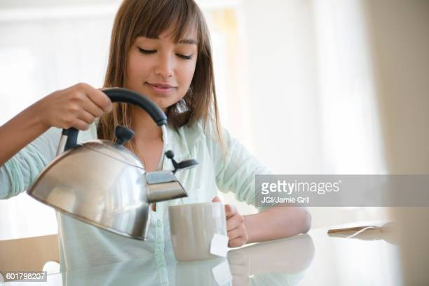 Mixed race woman pouring cup of tea