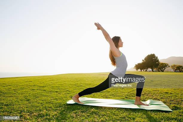 Mixed race woman practicing yoga in park