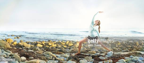 Mixed race woman practicing yoga on rocky beach