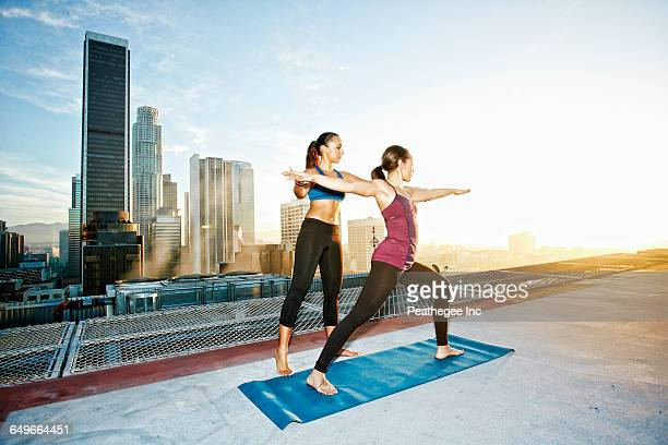 Mixed race woman practicing yoga on urban rooftop
