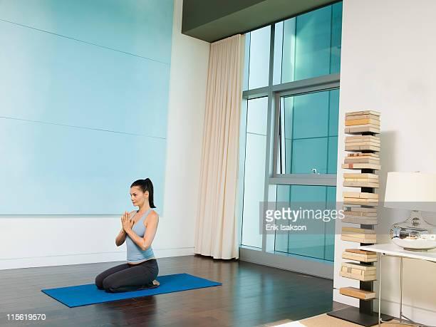 mixed race woman practicing yoga - mulher orando de joelhos imagens e fotografias de stock