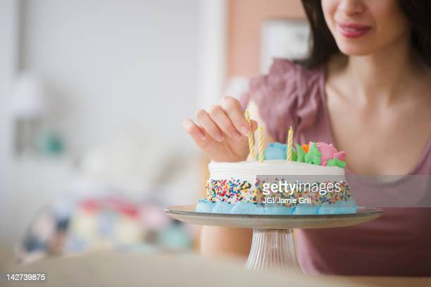 mixed race woman preparing birthday cake - positioning stock pictures, royalty-free photos & images