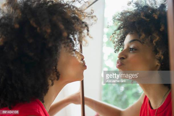 mixed race woman puckering in mirror - cara a cara imagens e fotografias de stock