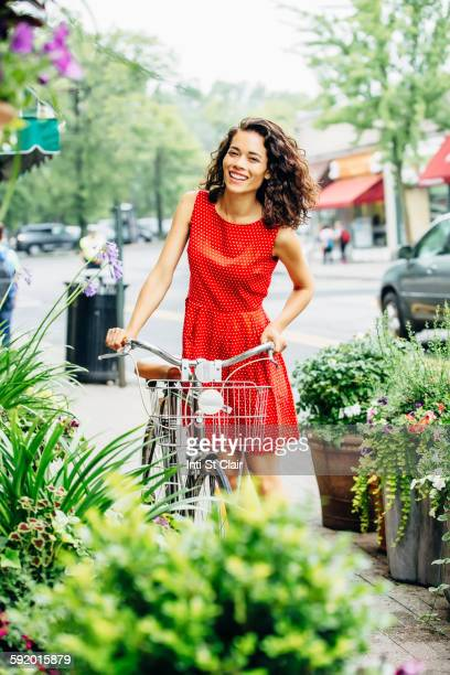 Mixed race woman pushing bicycle on city sidewalk