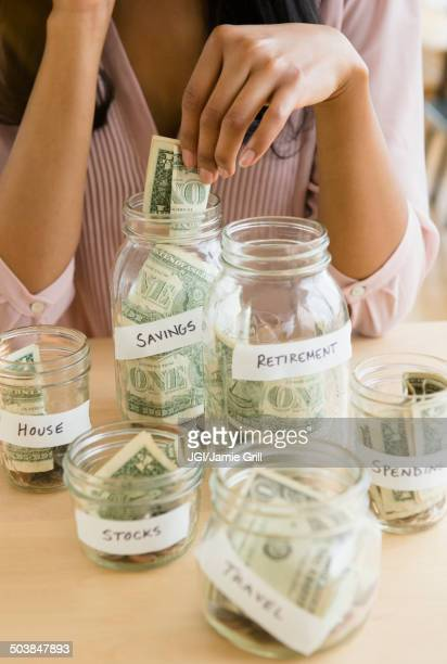 Mixed race woman putting money in savings jars