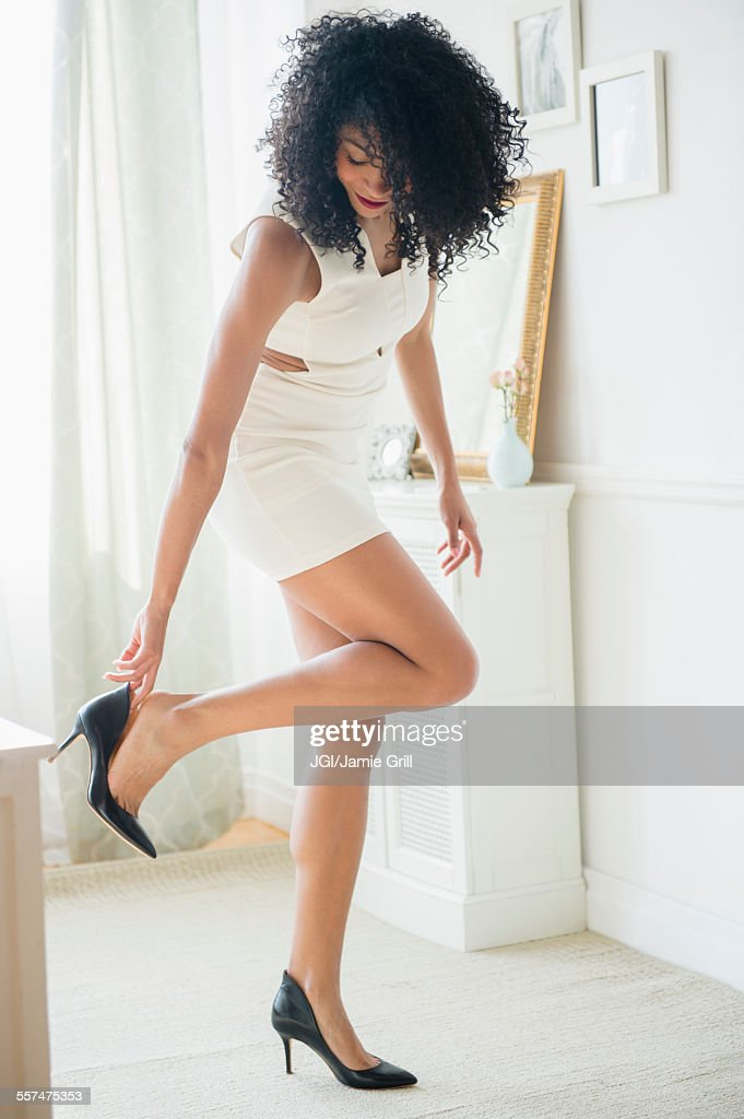 Mixed race woman putting on high heel shoes : Foto de stock