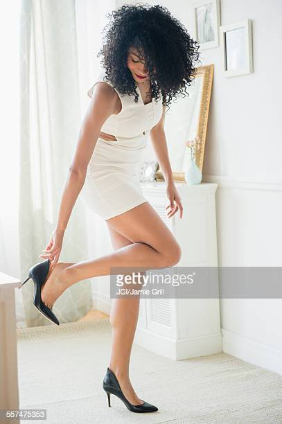 Mixed race woman putting on high heel shoes