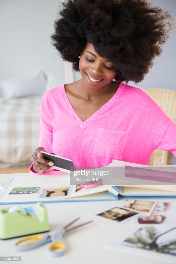 Mixed race woman putting photos in album : Stock Photo