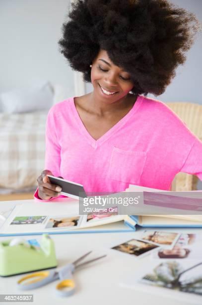 Mixed race woman putting photos in album