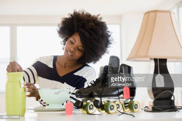 Mixed race woman putting price tag on items