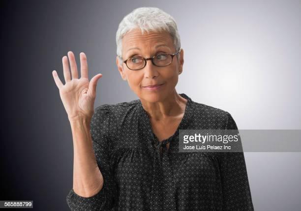 mixed race woman raising her hand - hand heben stock-fotos und bilder