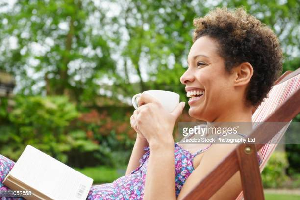mixed race woman reading book in backyard - spalding england stock photos and pictures