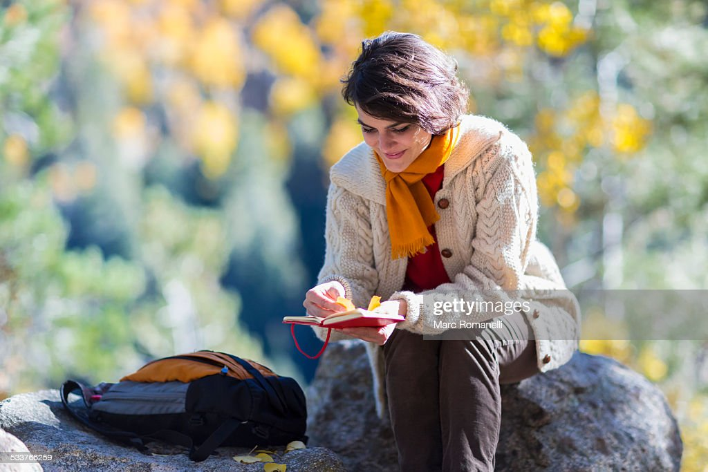Mixed race woman reading journal on rock : Foto stock